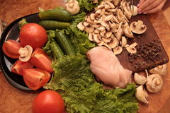 Cook chicken and vegetables. Love to healthy eating concept. Cooked chicken with mushrooms and a salad of tomatoes, cucumbers and greens. Proper nutrition. love Stock Image