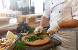 Cook chops parsley with a knife on  board Royalty Free Stock Photos