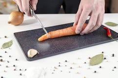 Cook ciie marchewki na czarnej tnącej desce zdjęcie royalty free