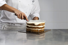 Cook coating a cake with cream Royalty Free Stock Photo