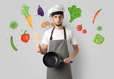Cook with colourful drawn vegetables. Bearded cook with colourful drawn vegetables on a white wallpaper stock images
