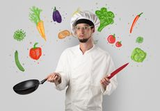 Cook with colourful drawn vegetables. Bearded cook with colourful drawn vegetables on a white wallpaper royalty free stock image