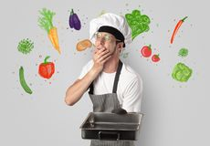 Cook with colourful drawn vegetables. Bearded cook with colourful drawn vegetables on a white wallpapern stock photos