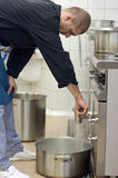 Cook in commercial kitchen. A male cook working in a commercial kitchen, emptying a boiling machine, pouring hot water into a large cauldron. Restaurant Royalty Free Stock Photography