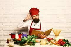 Cook with confused face in uniform sits by vegetables. Cook with confused face in uniform sits by table with vegetables, pasta and kitchenware. Cooking process stock photography