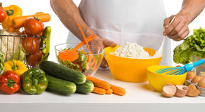Cook cooking cottage cheese with vegetables on table Stock Image