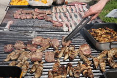 Cook while cooking in a grid of an outdoor barbecue for grilling Stock Photo
