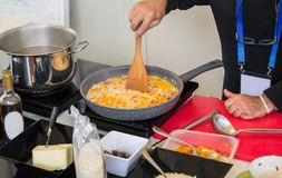 Cook cooking rise with vegetables in a pan Stock Photography
