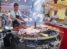 Cook cooking Sausages and Pork Ribs on a charcoal bbq. Madrid, Spain - May 15, 2018. Hispanic cook cooking Sausages, Pork Spare Ribs and others meats on a royalty free stock photo
