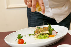Cook cooks fish dish - baked fillet of pikeperch, zander. Sprinkles with olive oil Stock Photo