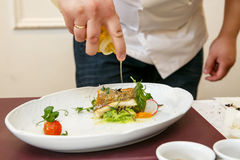 Cook cooks fish dish - baked fillet of pikeperch, zander. Sprinkles with olive oil Royalty Free Stock Photo