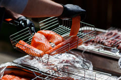 Cook cooks fish on grill. Cook in black gloves cooks red fish barbecue on grill Stock Photo