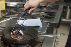 Cook cooks an octopus in a frying pan on a gas stove stock photo