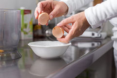 Cook cracking an egg Royalty Free Stock Photography