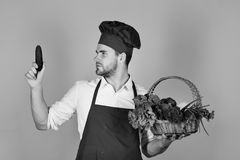 Cook with curious face holds cucumber and wicker basket of fresh veggies. Chef in burgundy uniform looks at cucumber in Stock Image