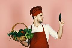 Cook with curious face holds cucumber and wicker basket of fresh veggies. Chef in burgundy uniform looks at cucumber in Stock Images