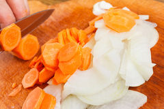 Cook cut onion and carrot on chopping board Stock Photos