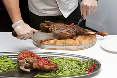 Cook cut up roast lamb leg Royalty Free Stock Image