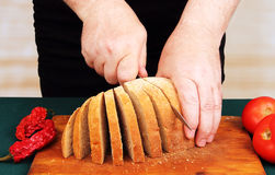 Cook cuts the bread. Royalty Free Stock Photos