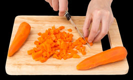 Cook cuts carrots on a board on a black background Royalty Free Stock Image