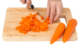 Cook cuts carrots on a white background Royalty Free Stock Photo