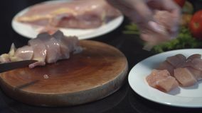 The cook cuts the chicken breast in half, raw chicken, chef cooks chicken breasts, poultry meat, diet meat stock video footage