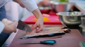 The cook cuts a fillet from fish skeleton. The cook cuts a fillet from the fish skeleton by knife at the table. The cook preparing fish at the kitchen of the stock video