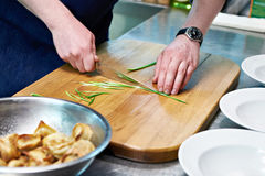 Cook cuts green onions for serving dumplings Stock Photo