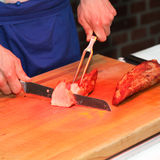 A cook cuts meat at the buffet Stock Image