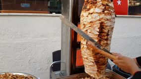 A cook cuts meat on a skewer to make shawarma. Turkish doner-kebab stock video footage