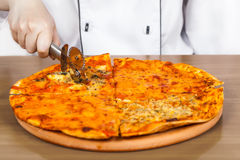 Cook cuts the pizza Royalty Free Stock Image