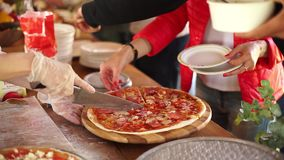 Cook cuts pizza with tomato sauce. stock video footage