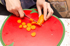 The cook cuts red carrots on a board Royalty Free Stock Images