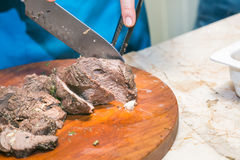 Cook cuts roasted beef meat. The concept of cooking. Cook cuts roasted beef meat Royalty Free Stock Photo