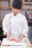 Cook cuts sushi rolls Stock Photo