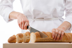 Cook cutting bread on wooden board Royalty Free Stock Images
