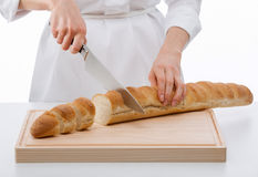 Cook cutting bread on wooden board Royalty Free Stock Photo