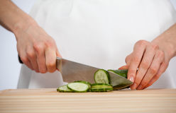Cook cutting fresh cucumber Stock Images