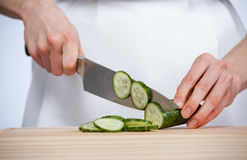 Cook cutting fresh cucumber Stock Photos