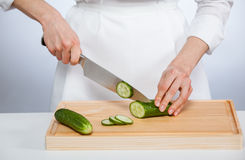 Cook cutting fresh cucumber Royalty Free Stock Photos
