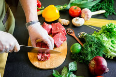 Cook cutting meat on a board and fresh raw vegetables on a dark background. Top view. Flat lay. Cook cutting meat on a board and fresh raw vegetables on a dark Stock Image