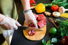 Cook cutting meat on a board and fresh raw vegetables on a dark table. Top view. Food concept. Cook cutting meat on a board and fresh raw vegetables on a dark Stock Image