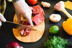 Cook cutting meat on a wooden board and fresh raw vegetables on dark table. Cook cutting meat on a wooden board and fresh raw vegetables on dark Stock Images
