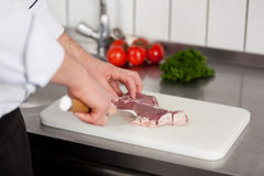 Cook cutting peace of meat Royalty Free Stock Photography