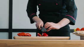 Cook cutting pepper on a cutting board stock footage