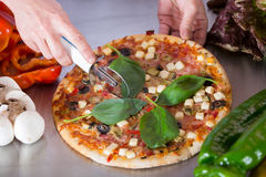 Cook cutting a pizza Stock Photo
