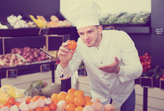 Cook deciding on best fruits in grocery store Stock Image