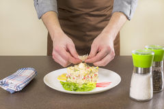 Cook decorate crab salad Royalty Free Stock Photos
