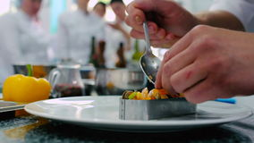 The cook decorating the dish in the restaurant. The chef accuracy put the vegetables on the shrimps stock video