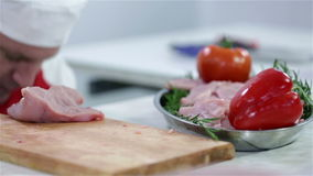 Cook decorating plate of turkey steaks with vegetables. Professional butcher preparing fresh turkey meat for cooking dishes and freezing in refrigerator for stock footage